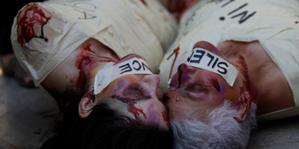 Spanish activist Jil Love and Mexican activist Julia Klug perform with tapes and fake blood during a protest against femicide and violence against women in Mexico City, Mexico